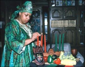 A woman lights kinara candles on a table decorated with the symbols of Kwanzaa  (Source:Wikipedia)